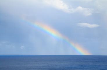 rainbow over the horizone at sea