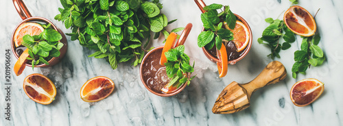Tuinposter Cocktail Flat-lay of blood orange Moscow mule alcohol cocktails with fresh mint and ice in copper mugs over white marble background, top view