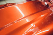 Car wrapping specialist putting vinyl foil or film on car wrapping protective film yacht, boat, ship, car, mobile home. orange film hand pulls