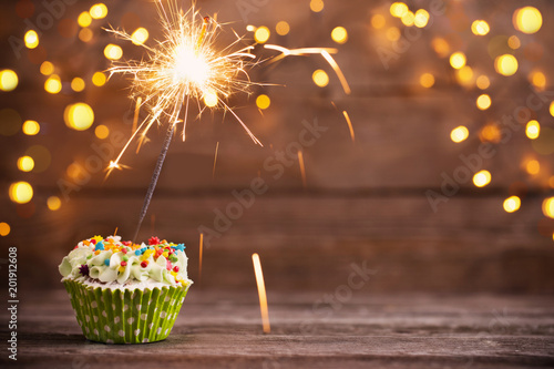 Fotografía cupcake with sparkler on old wooden background