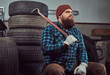 A bearded mechanic dressed in a uniform, sits on old car tires in the garage.