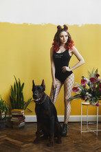 Sexy Hot Model Girl With Perfect Body, Red Hair And Bright Makeup, In Black Stylish Bodysuits And Mesh Pantyhose, Looks At Side And Posing With Angry Doberman In Interior