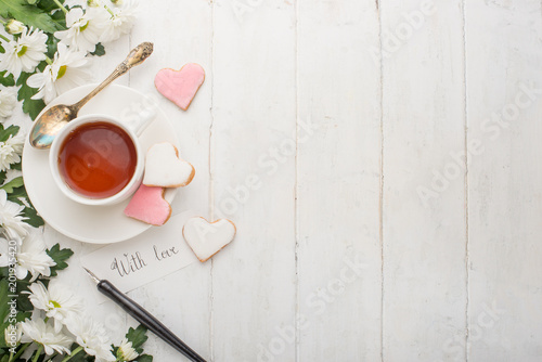 Tea with flowers and biscuits made with love. Top view with empty space for inscriptions