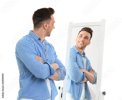 Obraz Young man looking at himself in mirror on white background - fototapety do salonu