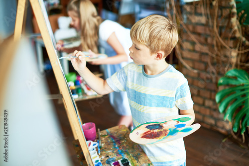 Fotografie, Obraz  Side view  portrait of blonde little boy painting on easel enjoying art class wi