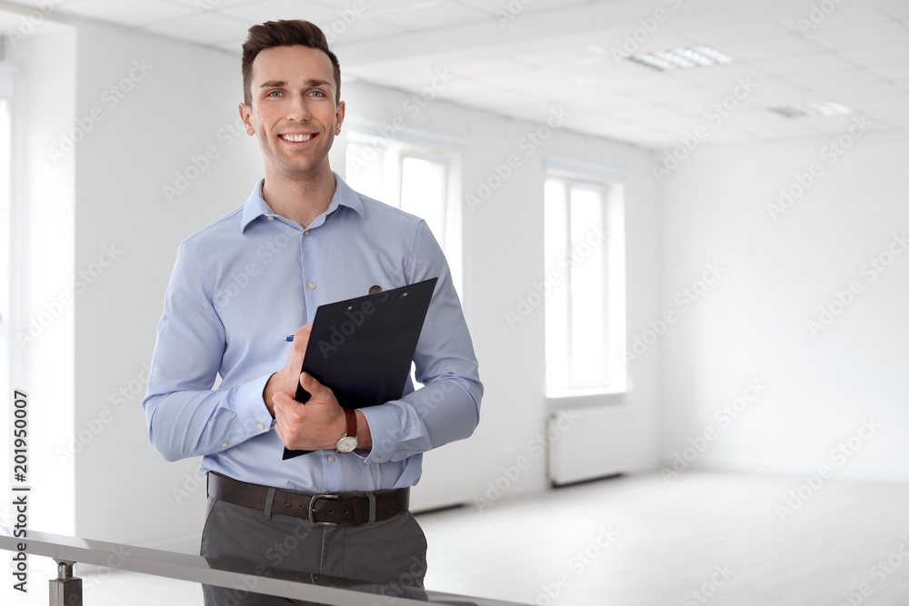 Fototapeta Male real estate agent with clipboard indoors