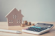 Leinwanddruck Bild - Calculator with wooden house and coins stack and pen on wood table. Property investment and house mortgage financial concept