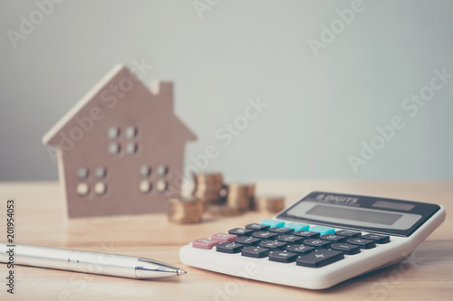 Fototapeta Calculator with wooden house and coins stack and pen on wood table. Property investment and house mortgage financial concept obraz