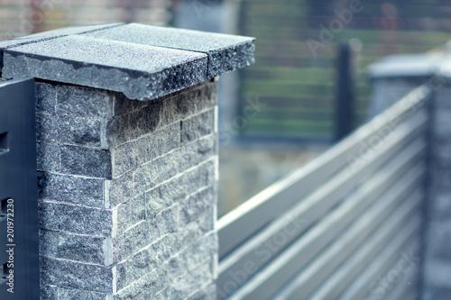 Obraz na płótnie Modern fence with stone pillars and metal filling