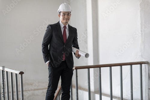 9d533684651b Businessman in white helmet with black suit and red necktie is walking on  the staircase. He is smiling ...