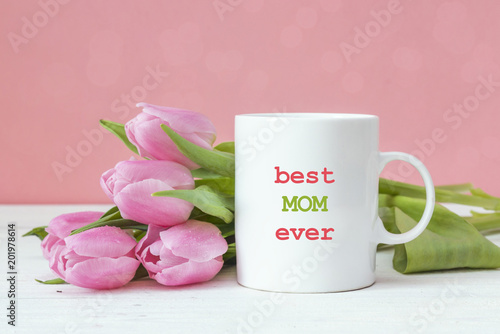 White coffee mug with Mothers Day greeting message and pink tulips on pink background.
