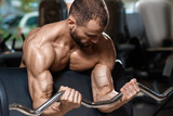 Strong man doing heavy weight exercise for biceps