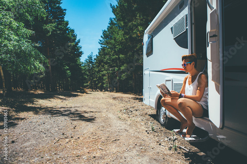 Girl reads on a motor home door step
