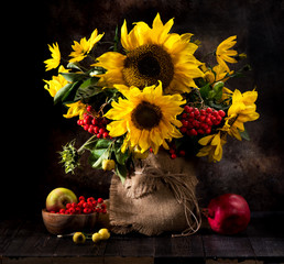 Fototapeta Do jadalni Still life bouquet of sunflowers in a vase, yellow autumn flowers, fruits and berries