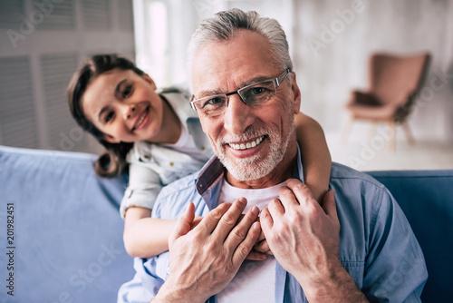 Fotografie, Obraz  The happy girl hugs a grandfather on the sofa