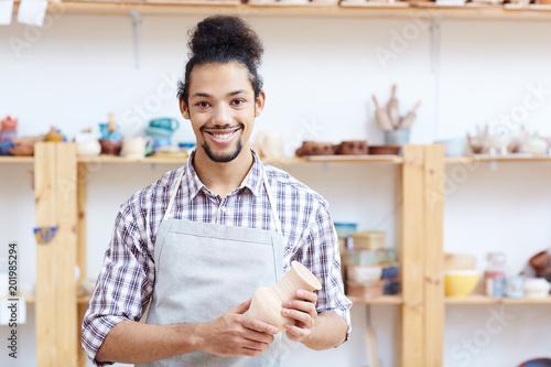 Foto  Porträt des jungen Mischrassemannes im Schutzblech, das in der Werkstatt mit han