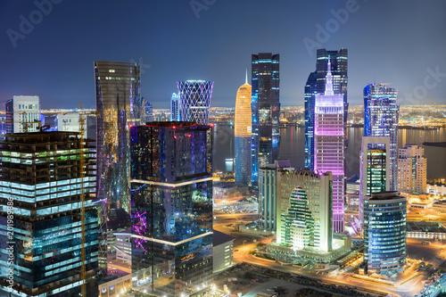 Das hell beleuchtete Zentrum von Doha, Katar, bei Nacht mit bunten Wolkenkratzern und der Westbay