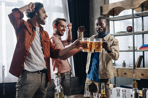 Bar excited male friends clinking beer glasses while partying together