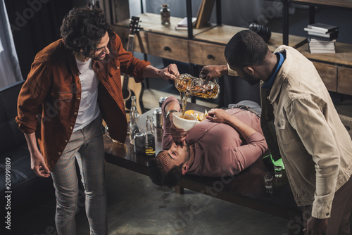 Bar multiethnic friends pouring beer in funnel and man drinking while lying on table
