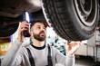 Man mechanic repairing a car in a garage.