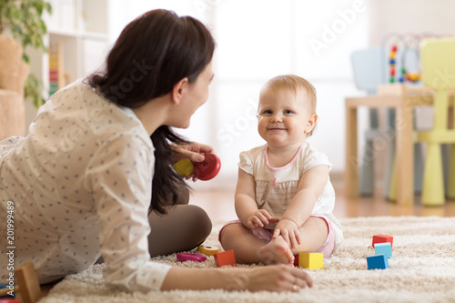 Photo Nanny or babysitter looks after kid toddler