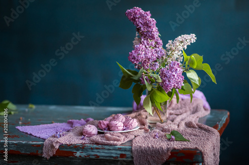 Fotobehang Lilac Bouquet of lilac flowers and marshmallows on old vintage table. Still life on dark blue background.