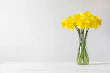 Daffodils In A Vase On A White...