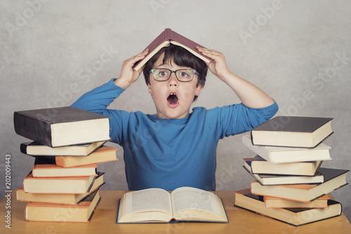 Foto  niño sorprendido con libros sobre una mesa