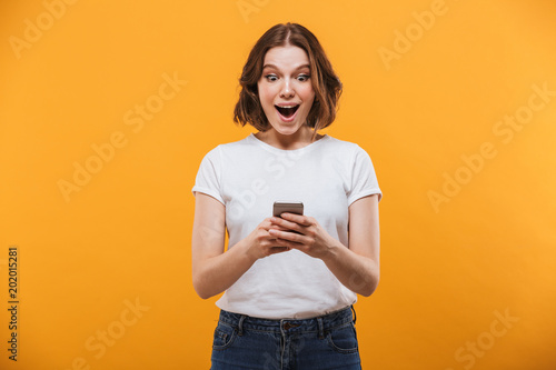 Fotografia  Excited young woman chatting by mobile phone