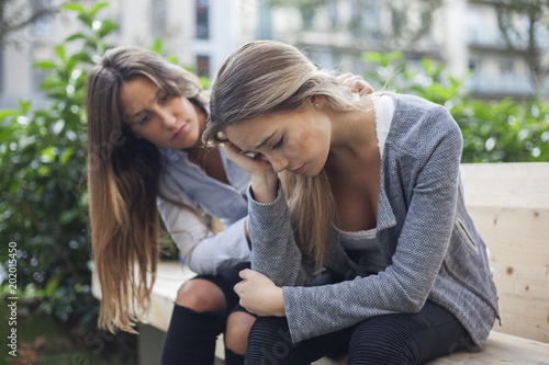 Fotografía  Woman comforting to a sad depressed friend who needs help