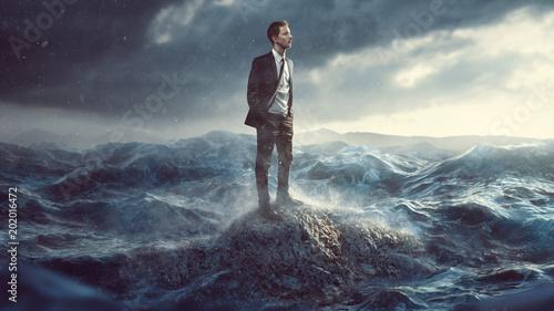 Valokuva  Geschäftsmann steht auf Fels in der Brandung