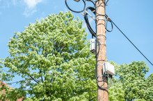 Electric Wires On Wooden Street Pole With Internet Or Cell Phone Communication Boxes And Blue Sky Background