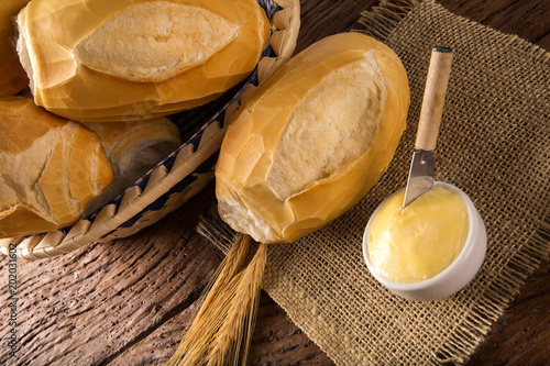 Valokuva  Basket of French bread, traditional Brazilian bread with butter on wood background