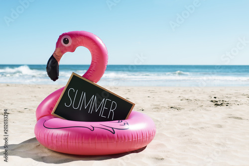 Foto op Aluminium Flamingo flamingo swim ring on the beach and text summer