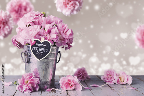 Happy mothers day letter on wood heart and pink carnation flowers in zinc bucket