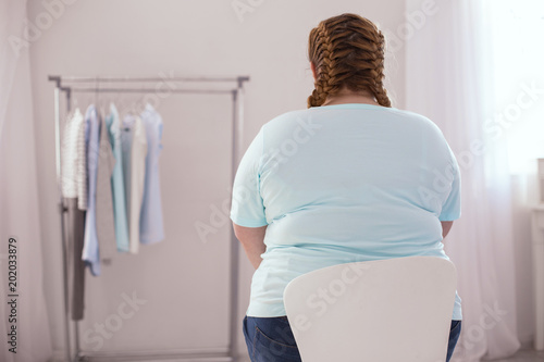 New clothes. Overweight young woman sitting on the chair while thinking about new clothes