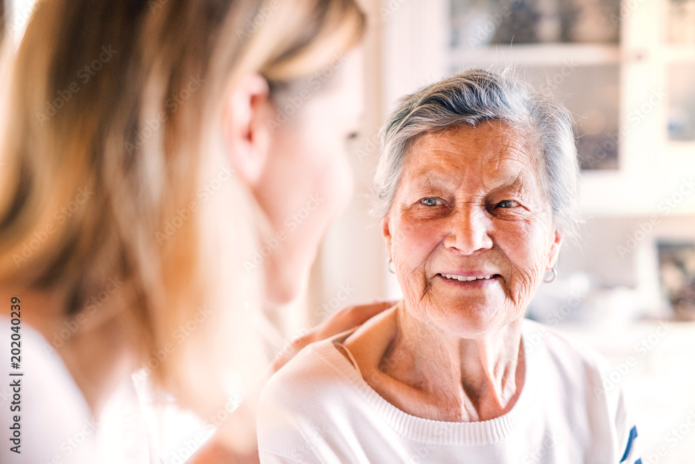 Fototapety, obrazy: An elderly grandmother with an adult granddaughter at home.