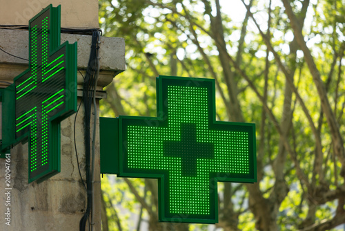 Closeup of a green pharmacy sign outside a pharmacy store in France.