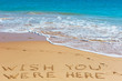 WISH YOU WERE HERE insctiption on wet beach sand with the turquoise sea on background