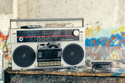 Plakat Retro boombox radio with cassettes / Vintage ghetto blaster with plenty of musical cassettes on grungy background with graffiti.