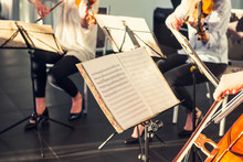 Selective Focus On Music Note Sheets On Stand With Background Of Playing Cellists And Violinists Band On Event In Bright Day Sunlight. Commercial Music. Service At Business Meeting, Party, Weddings.