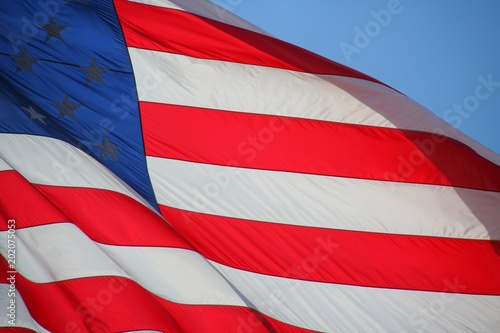 Photo Stands United States American Flag Waving Against Blue Sky Backlit by Morning Sun