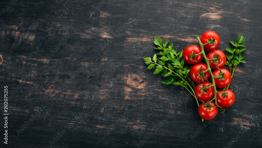 Fototapety, obrazy: Cherry tomatoes on a twig. Top view. On a black wooden background. Copy space.