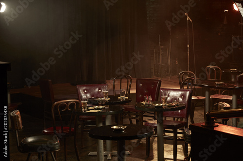 tables and chairs near stage in empty bar buy this stock photo and