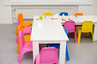 modern interior of the children's room in bright colors. shelves on the wall of the nursery in the form of stars. children's furniture: table and chairs. white wall.