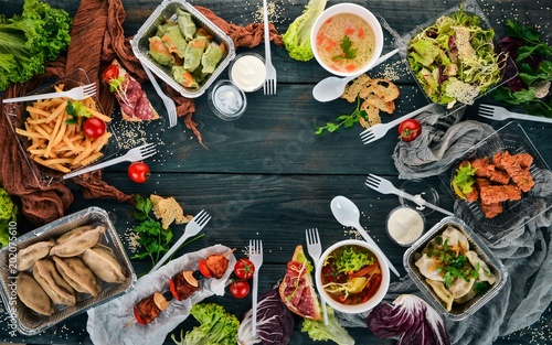 Food in lunch boxes. Delivery of food. Ukrainian cuisine. On a wooden background. Top view. Copy space.
