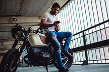 Handsome Man Sitting On His Motorcycle And Looking At Phone