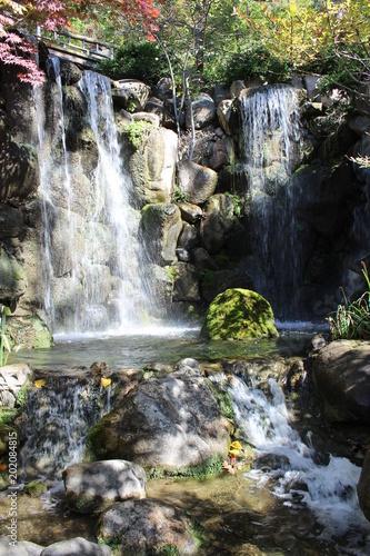 Naklejka premium Dwa wodospady z mostem nad nimi wpadającym do małego basenu