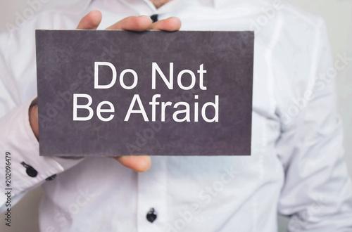Fotografía  Businessman showing Do Not Be Afraid word on cardboard.