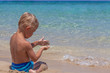 Boy playing in the sand and waves on the beach